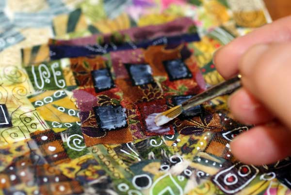 Adding gel medium on fabric surface. See instructions for creating fabric collages! By Peony and Parakeet.