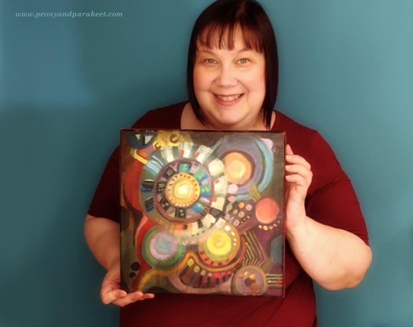 Paivi from Peony and Parakeet with her abstract painting made for the class Planet Color.