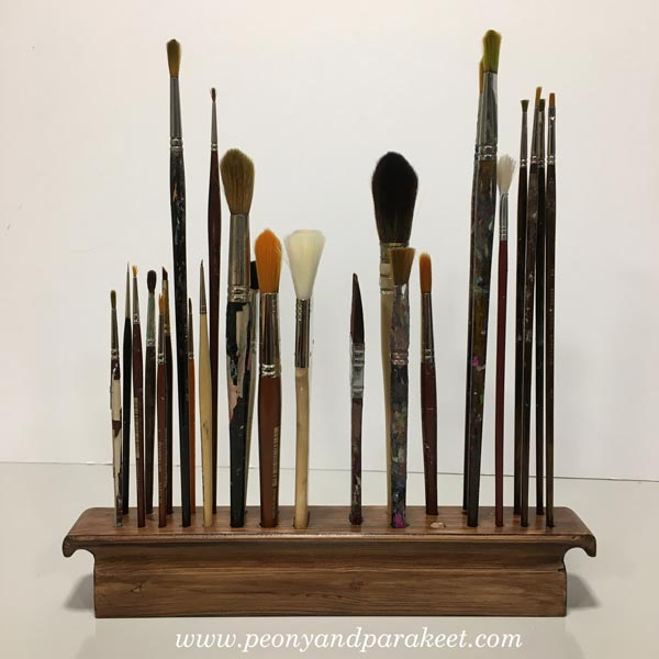 A wooden paint brush holder.