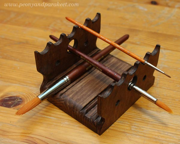 A wooden paint brush holder. Designed for wet brushes.