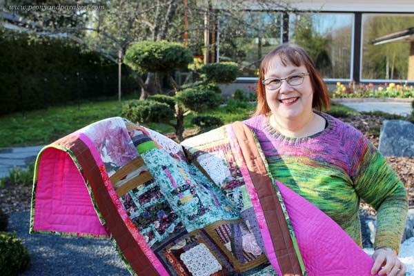 Paivi Eerola from Peony and Parakeet holding her hand-made quilt.
