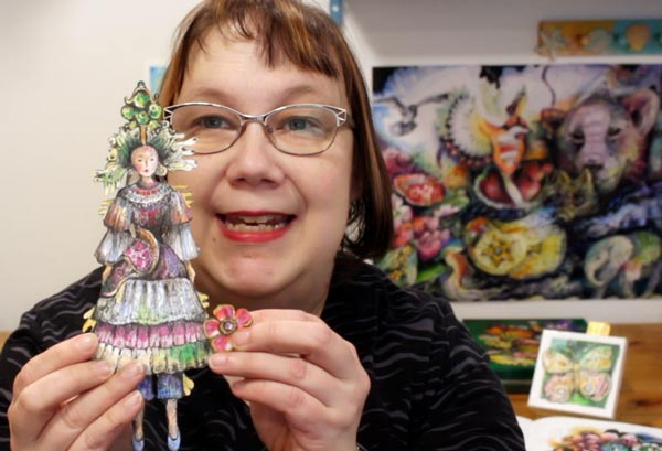 Paivi Eerola with one of her paper dolls showing the collage art pieces that she makes.