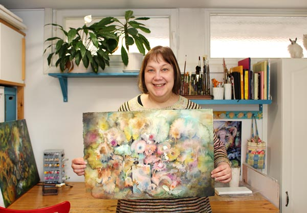 Paivi Eerola in her studio showing her watercolor painting Abracadabra.