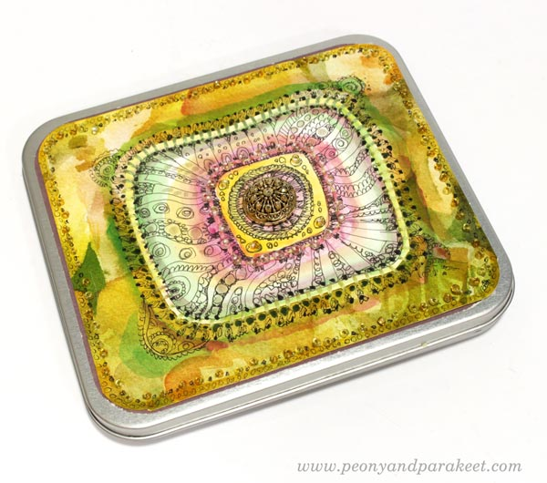 Decorating a tin box with beads, embroidery floss, and hand-drawn and hand-painted papers. Inspired by Sanditon tv series. By Paivi Eerola of Peony and Parakeet.