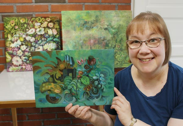 "Artist Paivi Eerola, Finland, holding ""Back to Nature"" and displaying her paintings in progress."