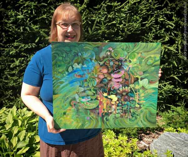 Artist Paivi Eerola holding a painting called Paradise, in her garden.