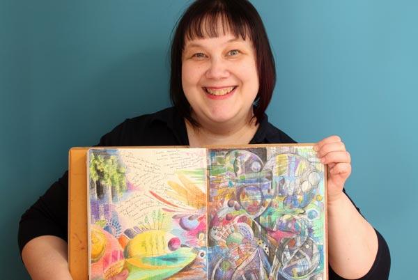 Artist Paivi Eerola holding one of her art journals.