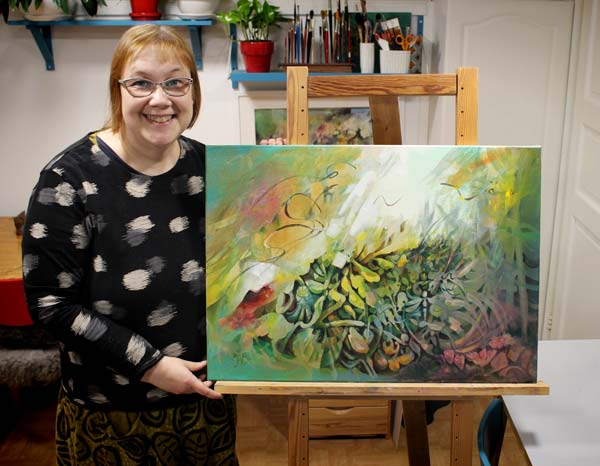 Artist Paivi Eerola holding her abstract painting Call of the Sun.