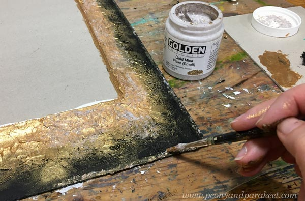 Adding gold mica flakes to a handmade frame.