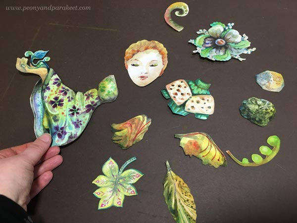 Arranging handpainted collage pieces.