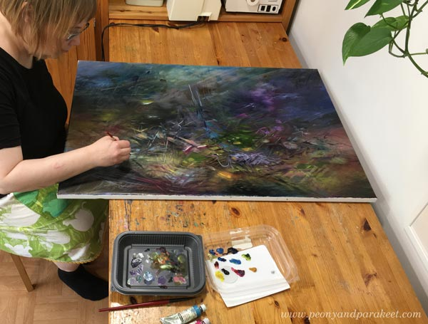 Paivi Eerola sitting in her studio and painting an oil painting. Read more about her mystical art.
