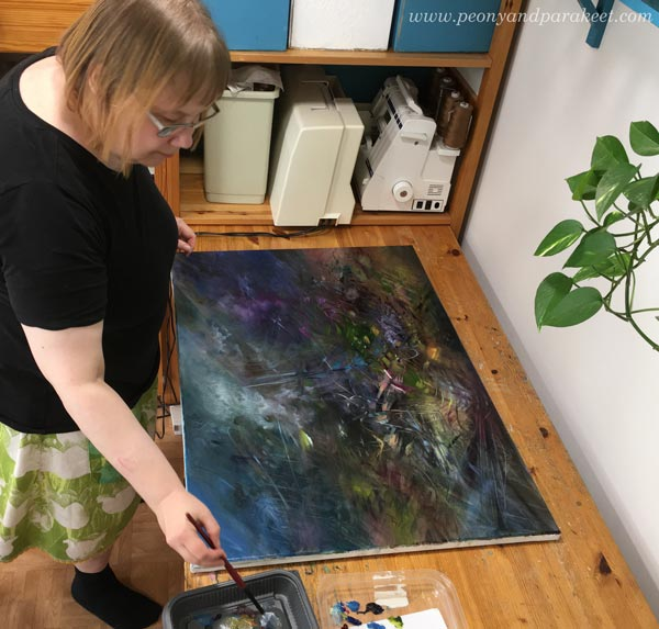 Paivi Eerola painting with oils. The painting is upside down.