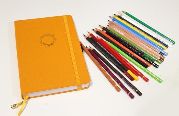 Archer & Olive notebook and a mixed selection of colored pencils.
