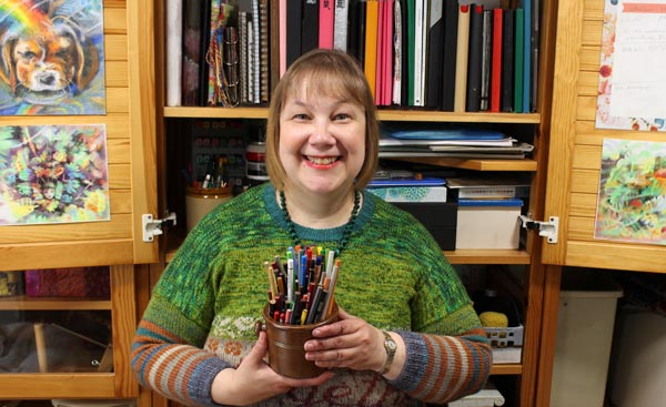 Artist Paivi Eerola and a jar of colored pencils.